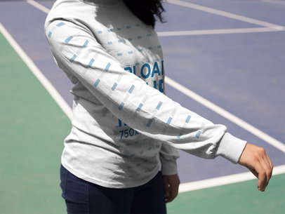 Girl Showing Her Right Arm While Wearing a Long Sleeve Tshirt Mockup at a Tennis Court a15980
