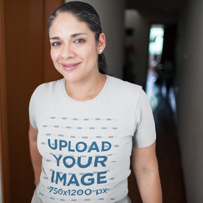 T-Shirt Mockup Being Worn by a Middle Aged Hispanic Woman Smiling While in a Hallway a16017