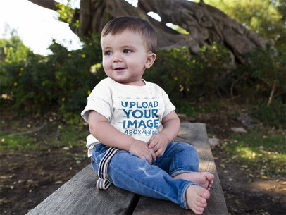 Cute Baby Boy Sitting Down in a Wooden Bench while Wearing a Round Neck Tshirt Template a16088