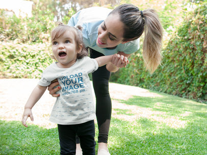 Smiling Little Girl Wearing a Tshirt Mockup While with Her Mom a16097