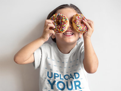 Boy Playing with Donuts While Wearing a T-Shirt Mockup Against a White Wall a16139