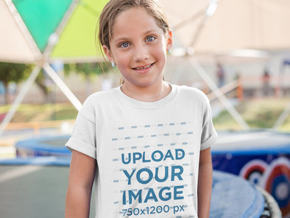 Smiling Little Girl Wearing a T-Shirt Mockup While Outdoors a16168