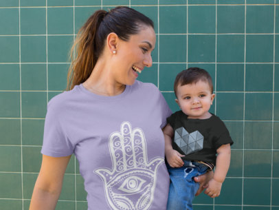 Baby and his Mom Wearing Different Round Neck Tees Mockup while Against a Green Tiles Wall a16095