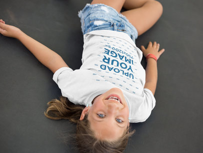 Little Blonde Girl Wearing a T-Shirt Mockup While Lying Down a16160