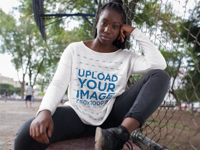 Pretty Girl Wearing a Round Neck Long Sleeve Heather Tee Template While Sitting Down Outdoors Against a Fence a16201