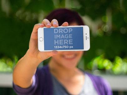 Woman Holing iPhone 6 Frontal Shot Bokeh