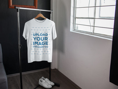 T-Shirt Mockup on a Rack Near White Shoes and a Window a16956