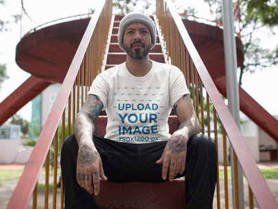Man Sitting on Wooden Stairs While Wearing a Round Neck Tee Mockup  a16987