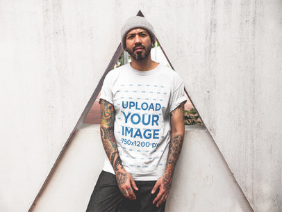Tattooed Man Wearing a T-Shirt Mockup While Lying Against a Triangle Structure a16986