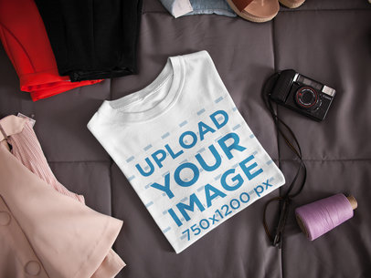 Folded T-Shirt Mockup Lying Next to a Camera and Clothes on a Bed a16941