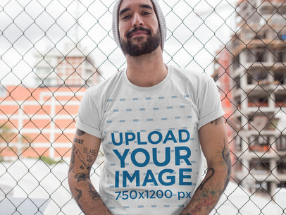 Hipster Middle Aged Man Wearing a Round Neck Tee Mockup While Lying Against a Fence a17020