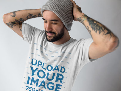 Mockup of a Man Fixing Up his Beanie While Wearing a T-Shirt at a Studio a17021