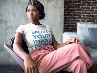 Mockup of a Woman Sitting by the Window at a Living Room Wearing a T-Shirt a17126