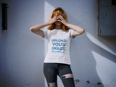 Girl Wearing a Halloween Tshirt Mockup While Covering her Face Against a White Wall a17105