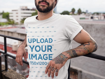 Cropped Face Tattooed Man Wearing a T-Shirt Mockup While Lying Against a Fence on a Rooftop a17027