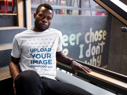 Mockup of a Black Guy Wearing a Round Neck Tee Template While Sitting on Stairs a17164