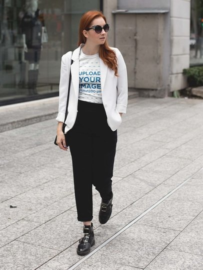 Mockup of a Fashion Girl Wearing a Tee Mockup and a White Jacket Walking in the City a17265