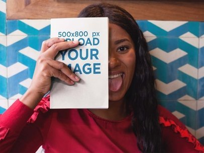 Black Girl Holding a Book Mockup Against her Face While Being Funny a17342