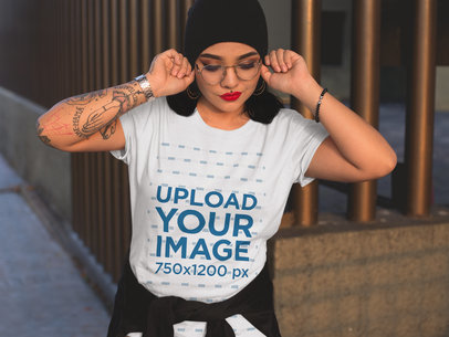 Tattooed Hispanic Girl Wearing a Round Neck Tee Mockup While Fixing her Glasses a17230