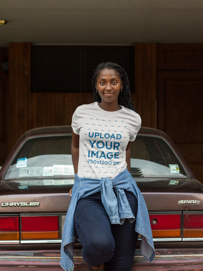 Smiling Black Woman Wearing a Round Neck Tee Mockup While Against a Vintage Car a17320