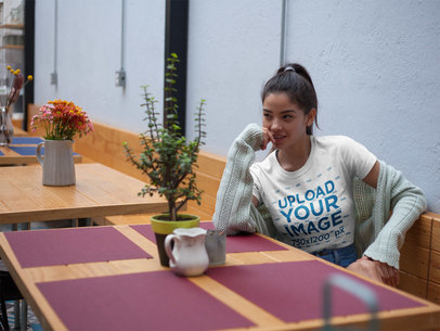 Pretty Girl Wearing a Round Neck Tee Mockup While Sitting on a Wood Table at a Cafe a17472