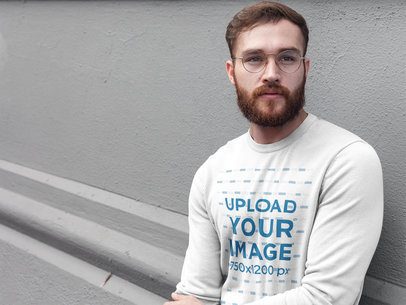 Redhaired Man with Beard Wearing a Crew Neck Sweatshirt Template While Lying Against a Wall a17722