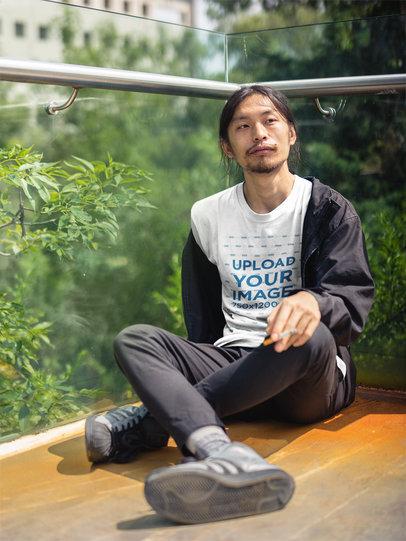 Asian Man Wearing a Round Neck Tshirt Mockup While Smoking at a Balcony a17789
