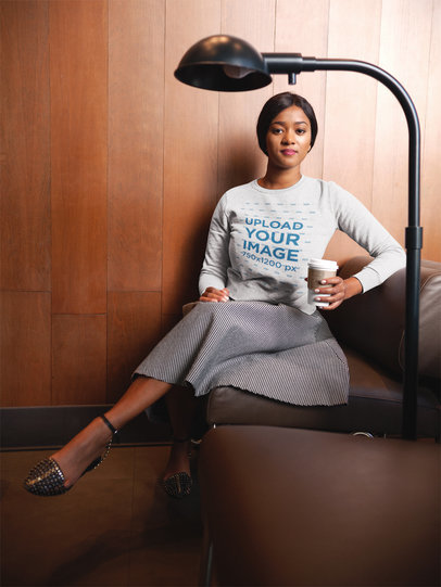 Beautiful Black Woman Wearing a Crew Neck Sweatshirt Template While Sitting on a Sofa a17751