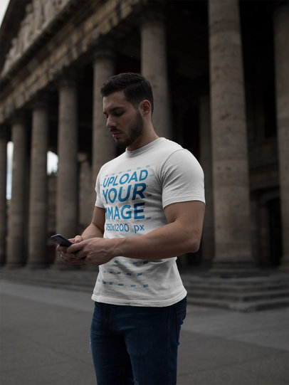 Strong Man Wearing a T-Shirt Mockup While Using his Phone Near a Historic Building a17662