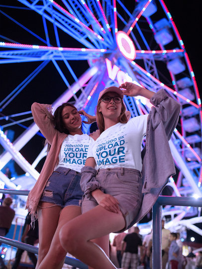 Two Girls Wearing T-Shirts Mockup Near a Ferris Wheel at Night a17879