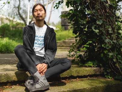 Asian Man Wearing a T-Shirt Template While Sitting at a Park a17787