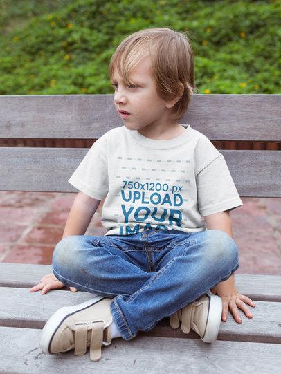 Sad Kid Wearing a Tshirt Mockup Sitting on a Bench a17954