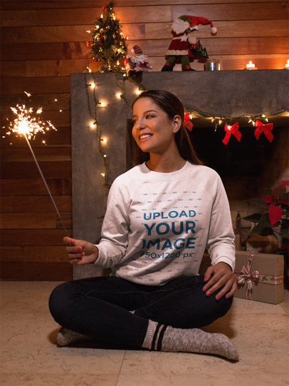 Beautiful Girl Wearing a Crew Neck Sweatshirt Template while Holding a Sparkler Next to a Small Christmas Tree a18044