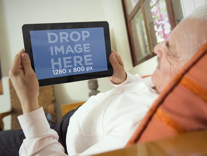 Elderly Man Laying On a Sofa With Android Tablet