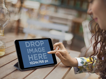 Mockup of a Pretty Girl Sitting on Outdoor Patio Using a Black iPad