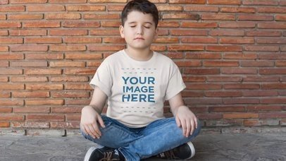 Kid's Tee Video Mockup of a Boy Sitting with his Legs Crossed a12772