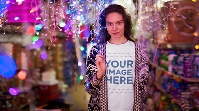 Stop Motion T-Shirt Mockup Video of a Young Woman Standing in Between Christmas Lights a13193-122016