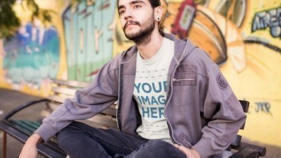 Trendy Young Man Sitting Outdoors Wearing a Round Neck Tee and a Grey Zip Up Hoodie Mockup Cinemagraph b13444