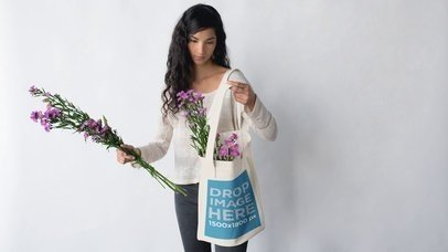 Pretty Girl Putting Flowers in her Tote Bag Against a White Background Mockup Stop Motion a13669