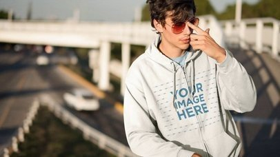 Cinemagraph Mockup Young Man Wearing Full Zip Hoodie and Sunglasses Near Highway a13333