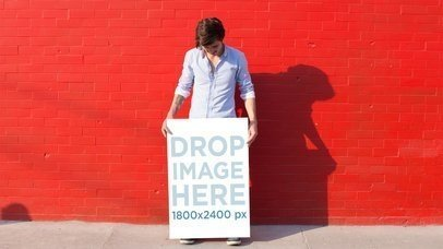 Handsome Young Man Being Funny While Holding a Poster Against a Red Wall Stop Motion Mockup a13658