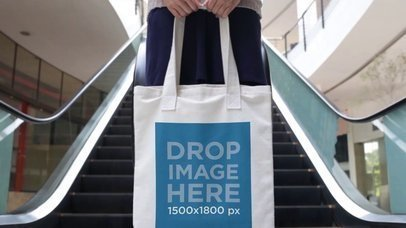 Cinemagraph Mockup Of A Girl Holding A Tote Bag While Escalators Moving In The Back a13769