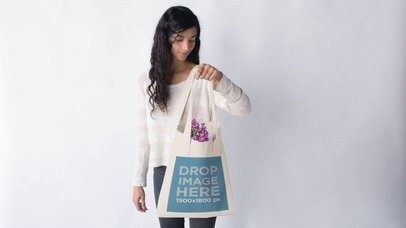 Young Pretty Girl With Tote Bag That Fills With Purple Flowers Against White Background Stop Motion Mockup a13670
