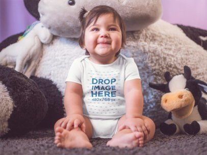 Mockup Of A Little Baby Girl Sitting Down While Smiling And Wearing A Onesie Near Her Teddy a14045