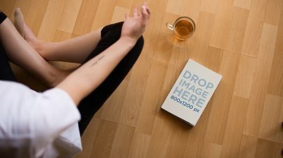 Video Mockup of a Book Lying on a Wooden Floor Besides a Meditating Girl a14171