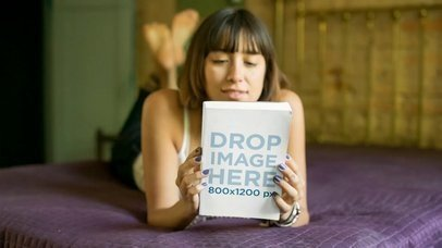 Young Girl Looking at a Book While in Her Purple Bed Video Mockup a14062