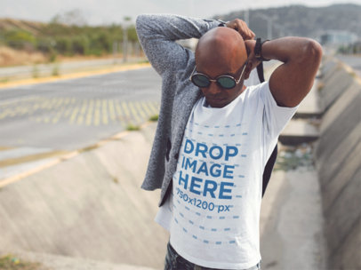 Mockup of a Black Man Wearing a Round Neck Tshirt and Steampunk Sunglasses While Outside of the City Template a14236