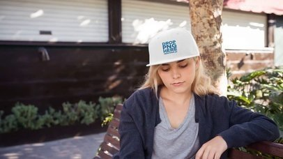 Young Girl Wearing a Snapback Hat While Sitting on a Bench Outdoors Mockup Video a14142