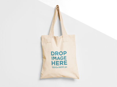 Tote Bag Mockup Hanging from a Nail on a Two Colors Wall a15313