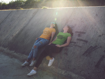 Two Girls Lying Down While at an Industrial Area Wearing Different T-Shirts Mockup a15711